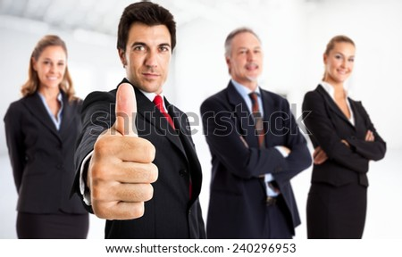 Portrait of a businessman giving thumbs up in front of his team