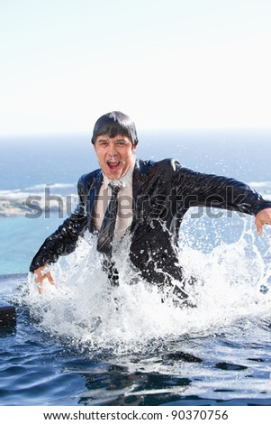 Portrait of a businessman going out of the water in a swimming pool - stock photo