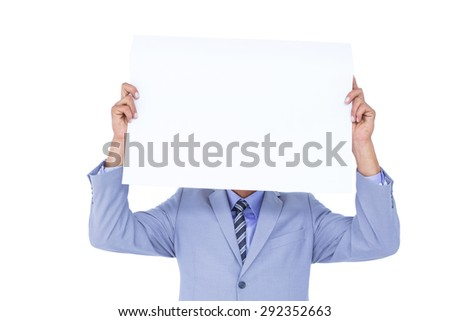 Portrait of a businessman hiding his face behind a blank panel against a white background