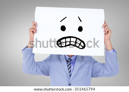 Portrait of a businessman hiding his face behind a blank panel against white background with vignette - stock photo