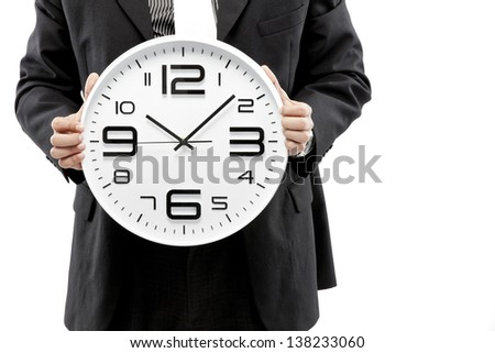 Portrait of a businessman holding a clock against white background