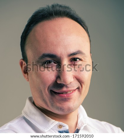 Portrait of a businessman in a shirt looking at the camera and smiling, age thirty-five, thirty-seven years