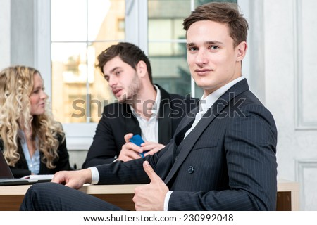 Portrait of a businessman in office. Businessman showing thumb up while talking to his colleagues in the background sitting at table - stock photo