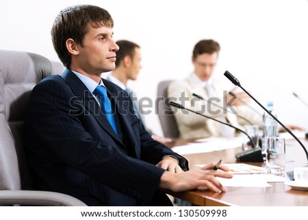 Portrait of a businessman, in the background colleagues communicate with each other - stock photo