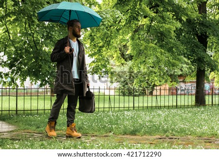 Portrait of a businessman in the park during rainy season. - stock photo