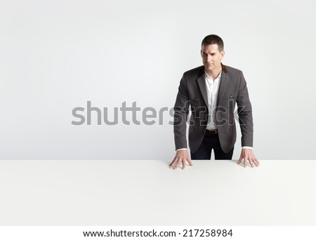 Portrait of a businessman leaning on white table - stock photo