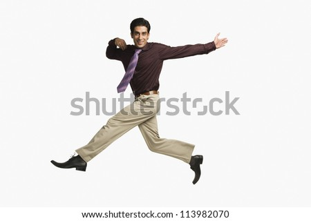 Portrait of a businessman leaping against a white background