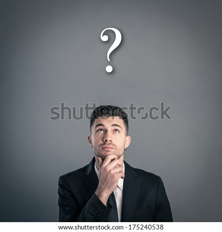 Portrait of a businessman looking at question mark on dark background. Studio shot.  - stock photo