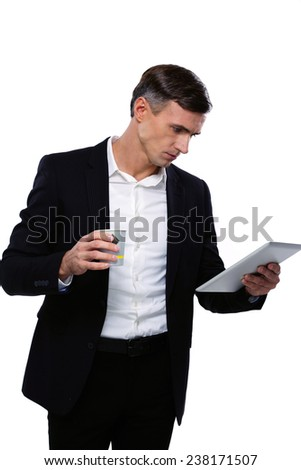 Portrait of a businessman looking at tablet computer and holding cup of coffee