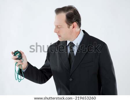 Portrait of a businessman, mature, bald, serious, wearing a suit and tie, looking at a stopwatch on white background - stock photo
