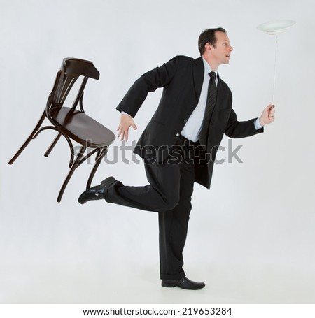 Portrait of a businessman, mature, bald, wearing a suit and tie, balancing a chair and a plate on a white background - stock photo
