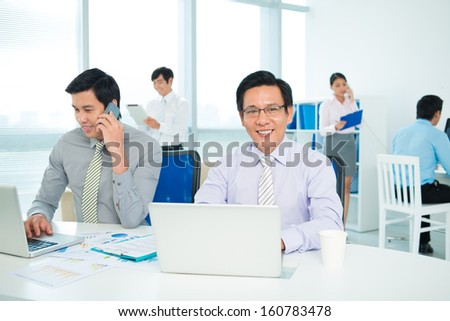 Portrait of a businessman networking on the workplace at the office on the foreground - stock photo