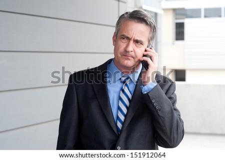 portrait of a businessman on the phone outside - stock photo