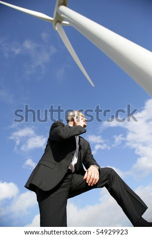 Portrait of a businessman phoning under a wind turbine