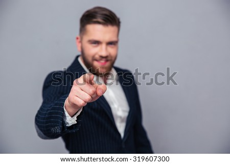 Portrait of a businessman pointing finger at camera over gray background. Focus on hand - stock photo