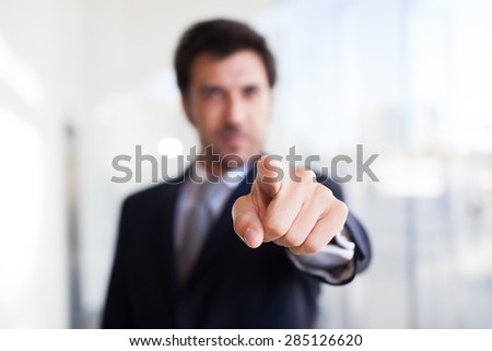 Portrait of a businessman pointing his finger to you