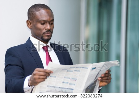 Portrait of a businessman reading a newspaper - stock photo