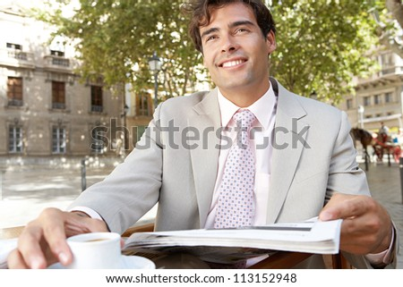 Portrait of a businessman reading the newspaper while having a coffee in a coffee shop terrace, smiling. - stock photo