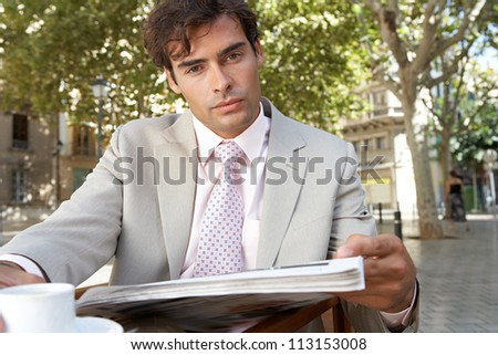 Portrait of a businessman reading the newspaper while having a coffee in a coffee shop terrace, outdoors.