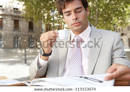 Portrait of a businessman reading the newspaper while having a coffee in a coffee shop terrace, outdoors. - stock photo
