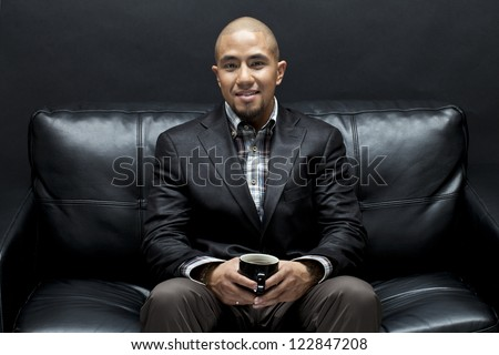 Portrait of a businessman relaxing on a couch with a coffee mug in hand - stock photo