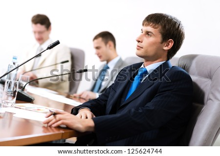 Portrait of a businessman, said into the microphone, in the background colleagues communicate with each other - stock photo