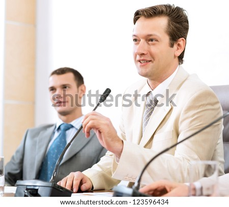 Portrait of a businessman, said into the microphone, the meeting