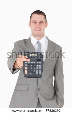Portrait of a businessman showing a calculator against a white background