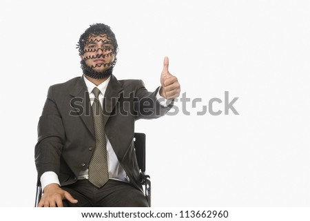 Portrait of a businessman showing thumbs up with his face covered with phone cord - stock photo