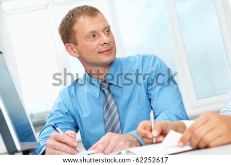 Portrait of a businessman sitting at table and looking away