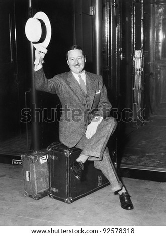 Portrait of a businessman sitting on his suitcases on a platform in front of a train - stock photo
