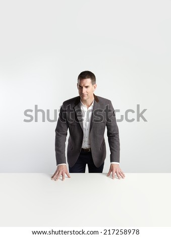 Portrait of a businessman standing behind white table - stock photo