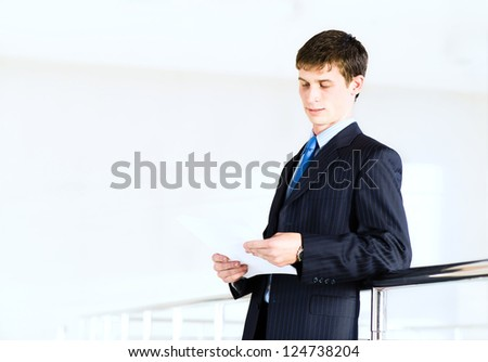 Portrait of a businessman standing in the office, keep the documents - stock photo