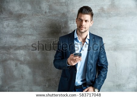 Portrait of a businessman. Successful good-looking young businessman with mobile phone.