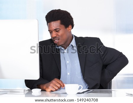 Portrait Of A Businessman Suffering From Back Pain - stock photo