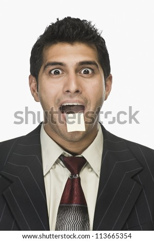 Portrait of a businessman surprised with an adhesive note on his lips - stock photo