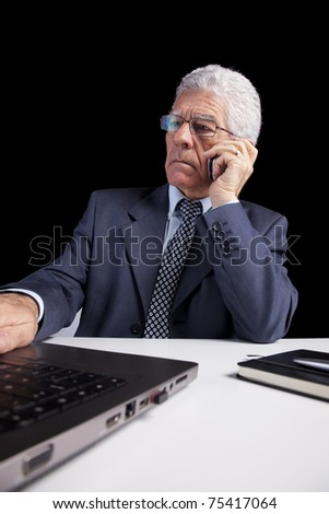 Portrait of a businessman talking at the mobile phone and looking to his laptop (isolated on black) - stock photo