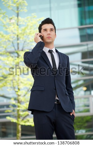 Portrait of a businessman talking on cellphone outdoors - stock photo