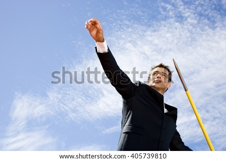 Portrait of a businessman throwing a javelin - stock photo