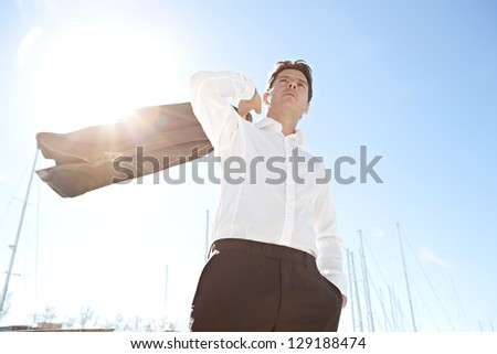 Portrait of a businessman throwing his jacket over his shoulder by a marine with the sun filtering through against a blue sky. - stock photo