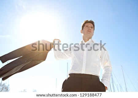 Portrait of a businessman throwing his jacket over his shoulder by a marine with the sun filtering through against a blue sky.