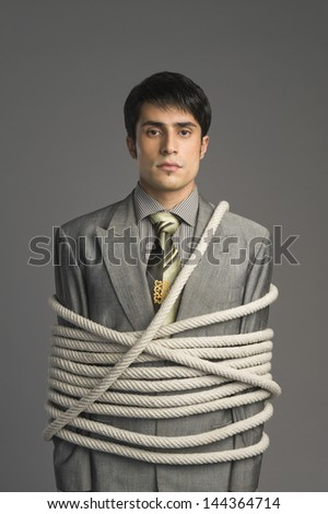 Portrait of a businessman tied up with ropes - stock photo