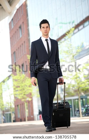 Portrait of a businessman traveling with bag - stock photo