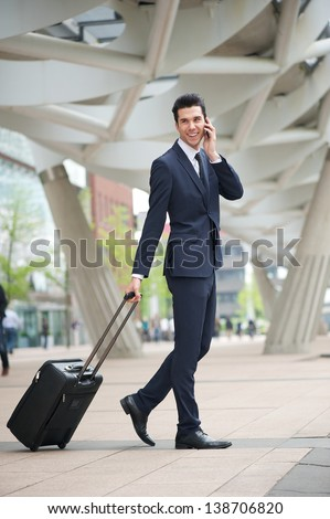 Portrait of a businessman traveling with phone and bag - stock photo