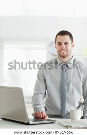 Portrait of a businessman using a laptop while drinking tea in his kitchen - stock photo