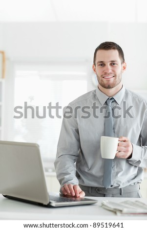 Portrait of a businessman using a notebook while drinking coffee in his kitchen - stock photo