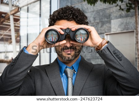 Portrait of a businessman using binoculars, people portraits reflected in the lens - stock photo