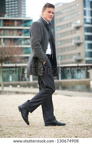 Portrait of a businessman walking outdoors - full length - stock photo