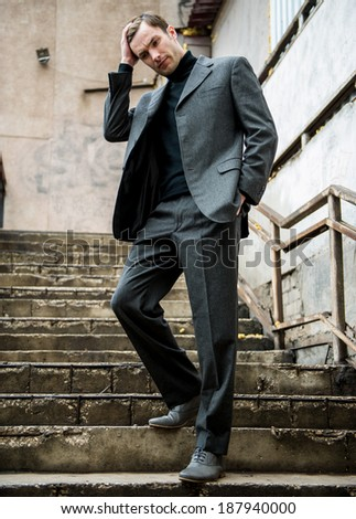 Portrait of a businessman who goes by the old stairs and thinks  - stock photo