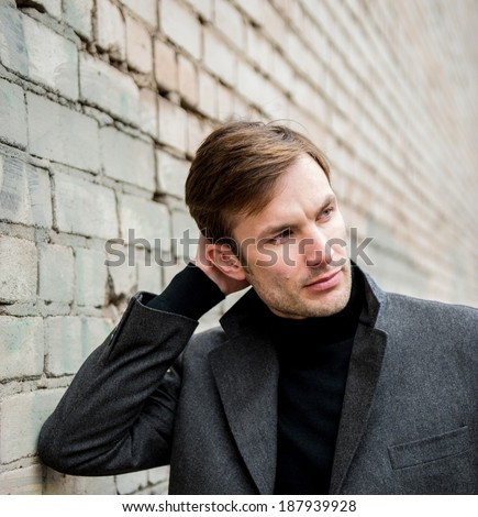 Portrait of a businessman who is focused and looking away against a brick wall, close-up  - stock photo